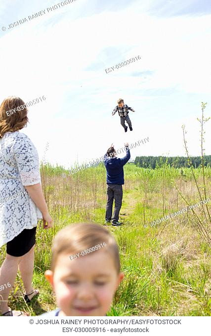 Family photo of a mother, father, and their two kid boys outdoors in a natural field in Oregon