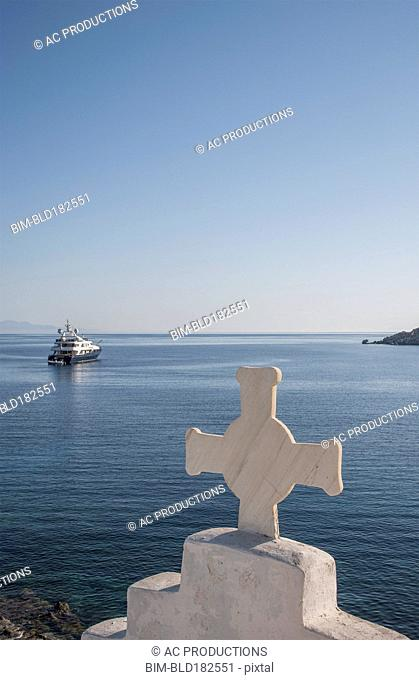 Cross on traditional arch and seascape