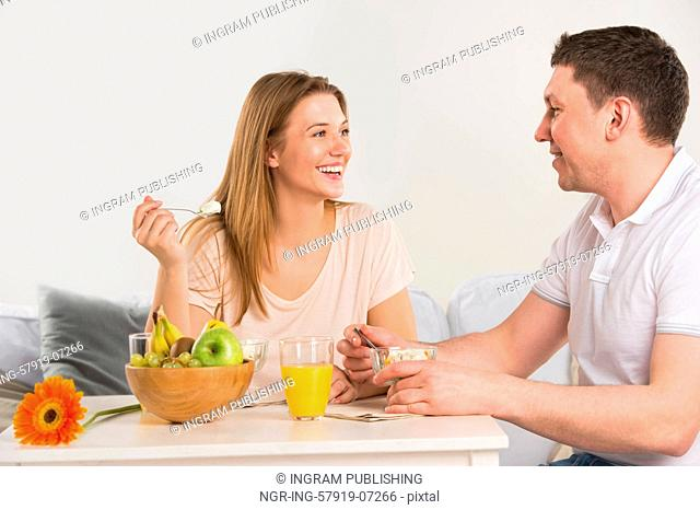 Happy couple eating at home - having breakfast together