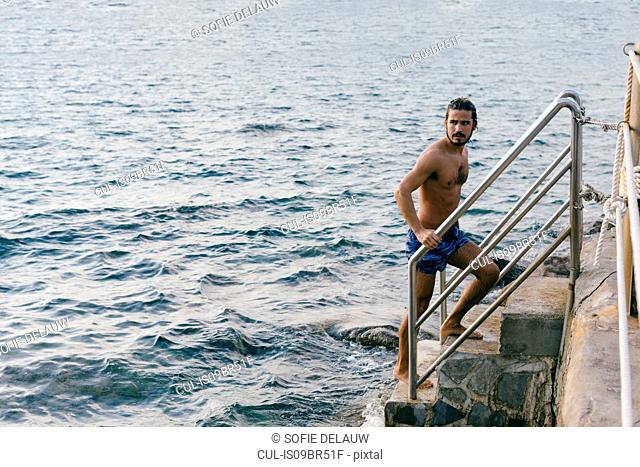 Man going up steps from sea