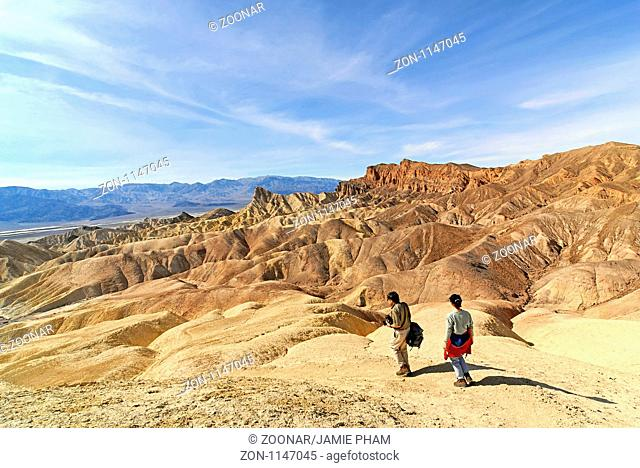 Two people hiking Zabriskie Point in Death Valley California