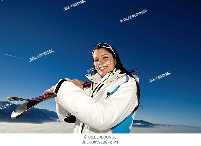portrait of young woman in the mountains carrying skis