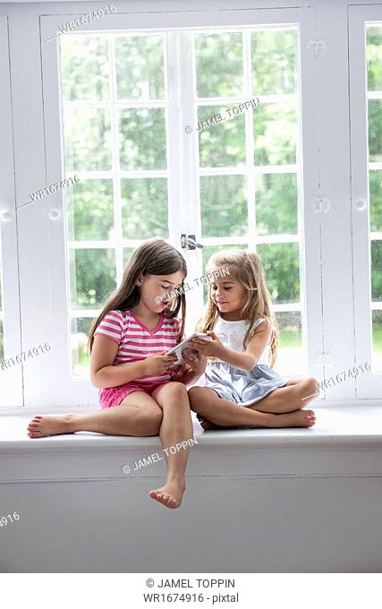 Two girls playing, sharing a digital tablet