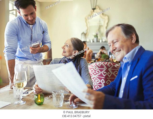 Waiter taking order from senior couple with menus at restaurant table