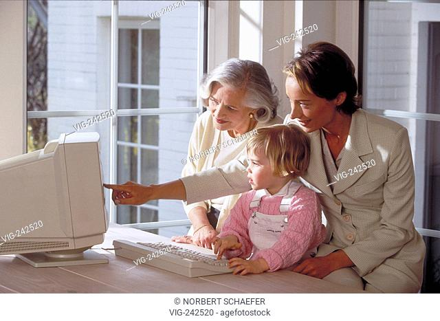 indoor, blond girl sits with her mother and her grandmother at the table near the window in front of the computer  - GERMANY, 26/02/2005