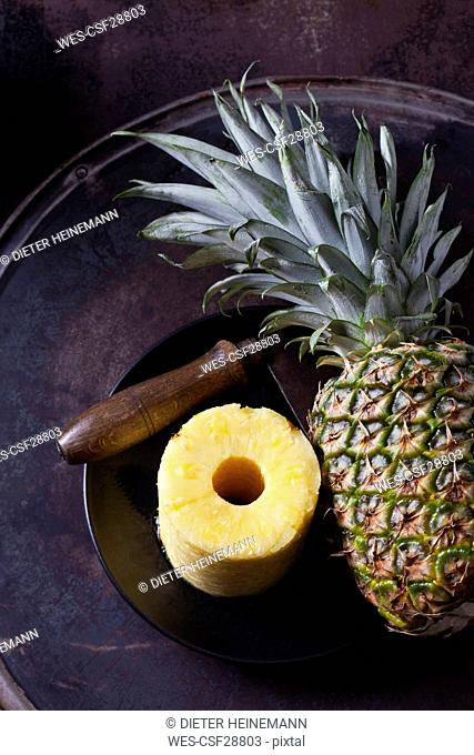 Stack of pineapple slices, whole pineapple and cleaver