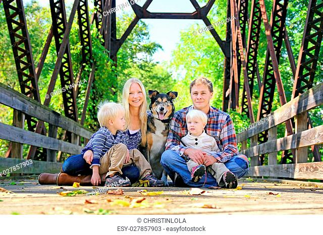 A portrait of a happy family of four people, including mother, father, young child, and baby brother and their pet German Shepherd Mix dog are sitting on an old...