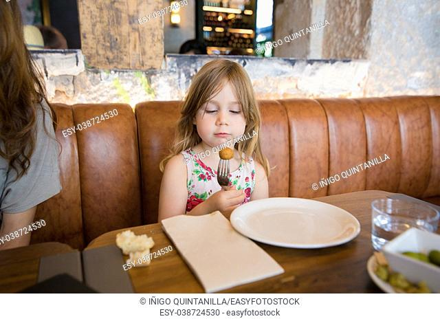 Four years age blonde girl eating and looking at croquette in fork next to woman mother sitting in brown leather sofa at restaurant