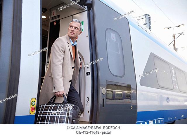 Businessman getting off passenger train