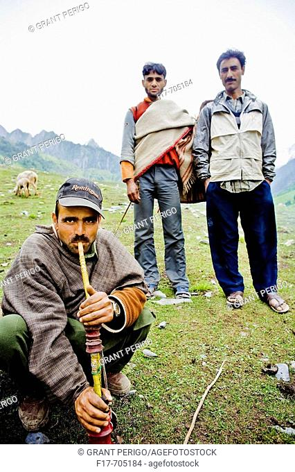 man smoking pipe on a hillside in the mountains in Kashmir