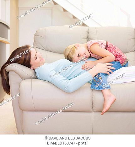 Caucasian girl listening to stomach of pregnant mother on sofa
