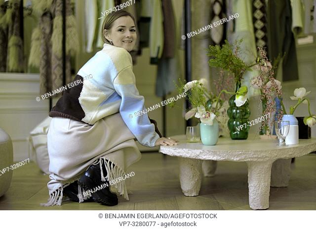 wealthy fashionable woman at home in living room, wearing latest designer fashion outfit, new trends during fashion week, in Paris, France