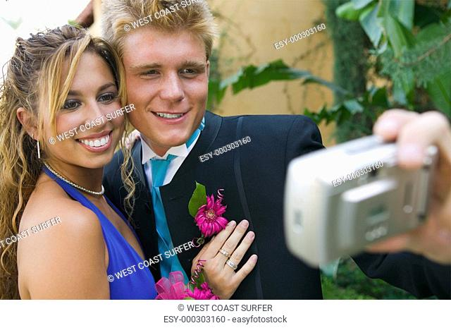 Well-dressed teenager couple taking picture outside school dance