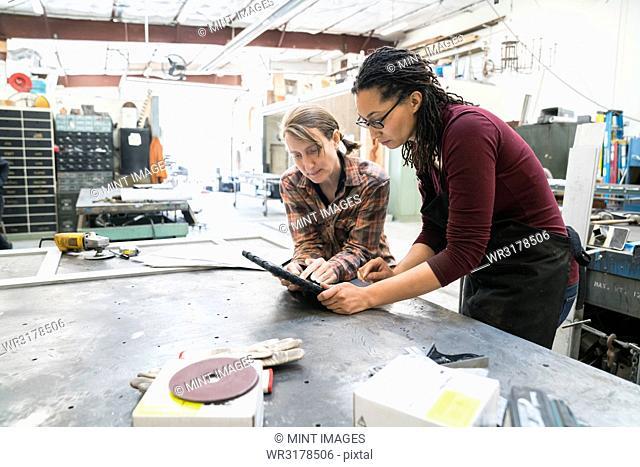 Two women standing at workbench in metal workshop, looking at digital tablet