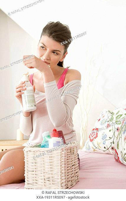 Young woman choosing body milk
