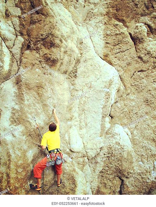 Rock climber reaching for his next hand hold, Joshua Tree National Park