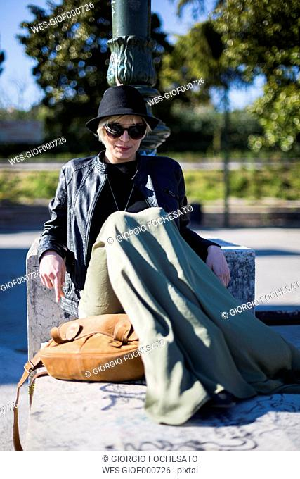 Portrait of blond woman wearing sunglasses and hat having a rest