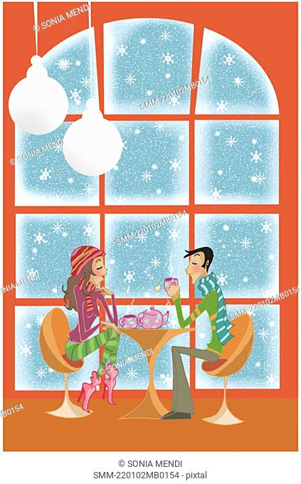 Young couple having tea while it's snowing outside