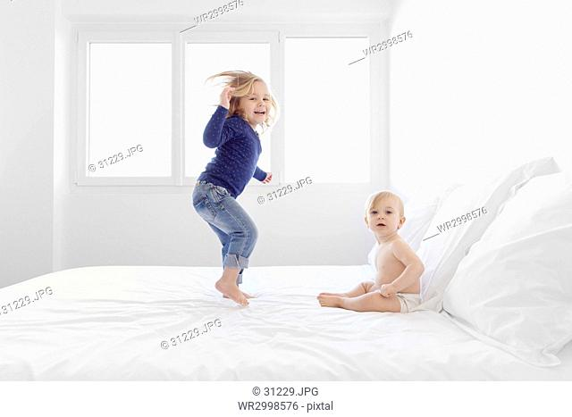 Girl with blond hair wearing jeans and blue top jumping on a bed, baby boy sitting beside her