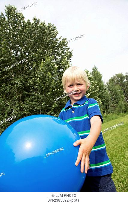 A young boy with blond hair plays with a large blue ball on the grass; Stony Plain, Alberta, Canada