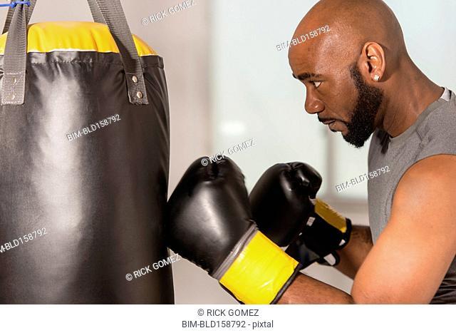 Black boxer training with punching bag