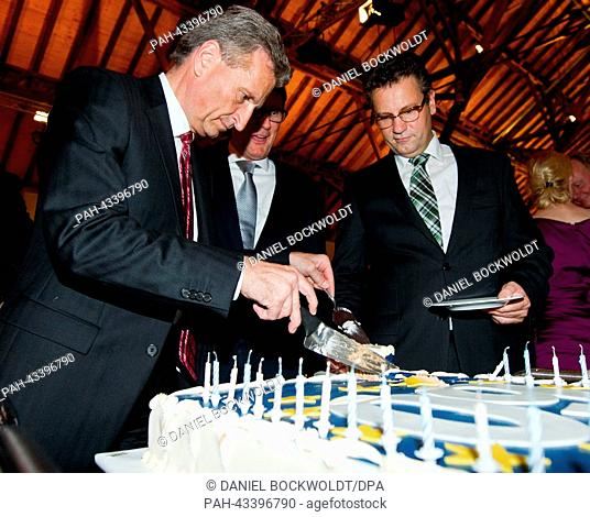 Former Premier of Baden-Wuerttemberg and current EU Energy Commissioner Guenther Oettinger cuts his cake next to chairman of the Baden-Wuerttemberg CDU Peter...