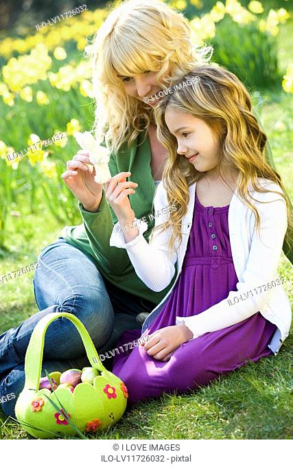 Mother and daughter looking at a toy Easter bunny