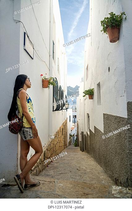 A Chinese young woman standing against a white residential building in a narrow street; Mojacar, Almeria, Spain