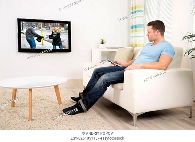 Full length of mid adult man with remote control watching movie in living room