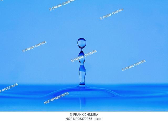 blue droplet hitting the water surface splashing it up
