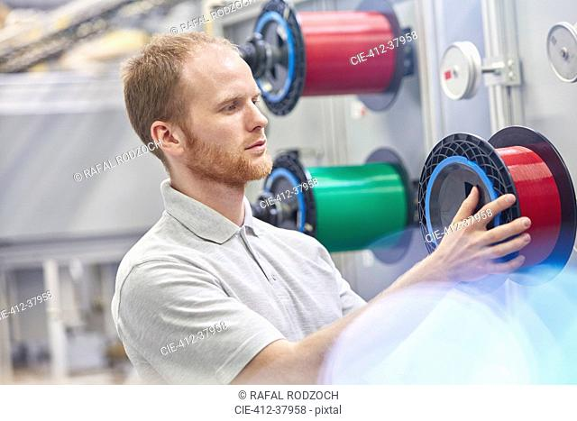 Male worker changing spool in fiber optics factory