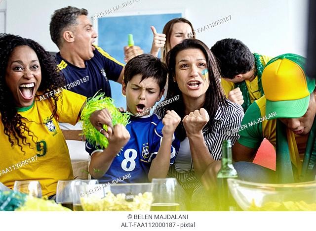 Brazilian football fans celebrating victory while watching match at home