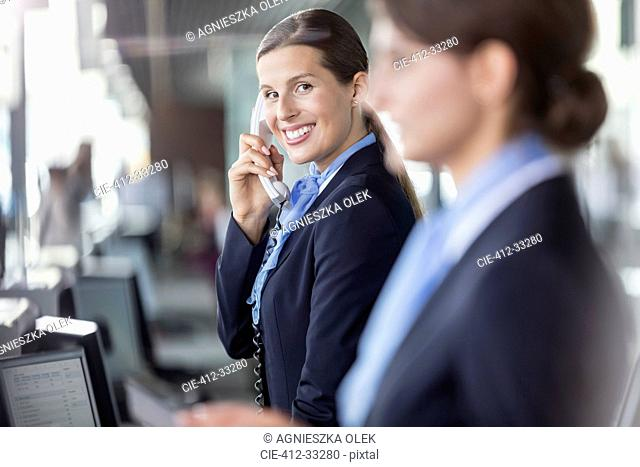 Portrait smiling customer representative talking on telephone at airport check-in counter