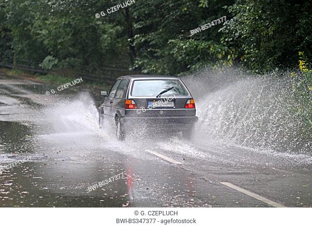 road traffic on flooded road in heavy rain, Germany