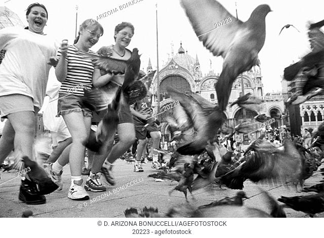 three young caucasian girls giggle with glee hand in hand as they run through a cloud of disturbed pigeons in front of St