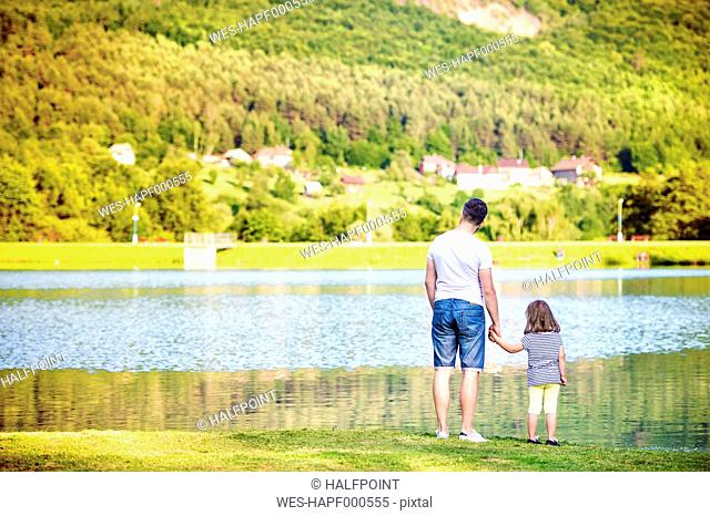 Back view of father and his little daughter standing at water's edge