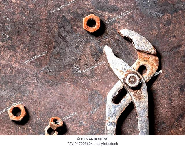 Old rusted tool and screws on grunge texture background. Industrial background