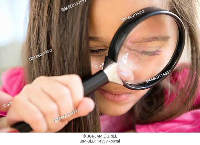 Hispanic girl using magnifying glass