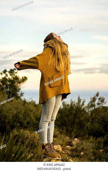 Young woman standing outdoors enjoying the nature