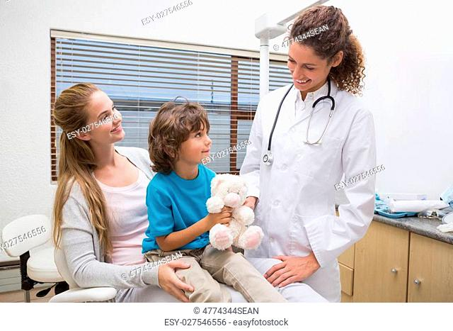Pediatric dentist smiling at little boy with his mother at the dental clinic