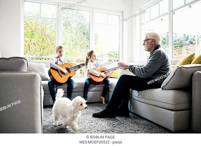 Two girls on sofa playing guitar with grandfather and dog
