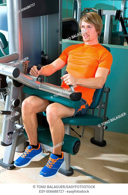 Gym seated leg curl machine exercise blond man at indoor