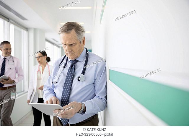 Male doctor using digital tablet in clinic corridor