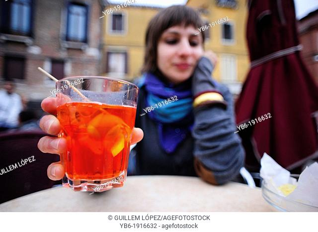 A young woman drinking an Aperol Spritz in Venice, Italy