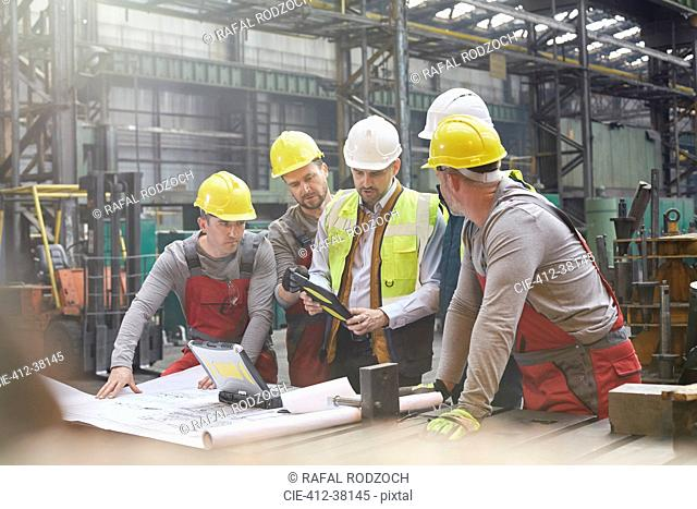 Male foreman, engineers and workers with digital tablet meeting in factory