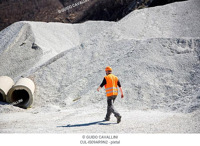 Quarry worker walking through gravel mounds at quarry