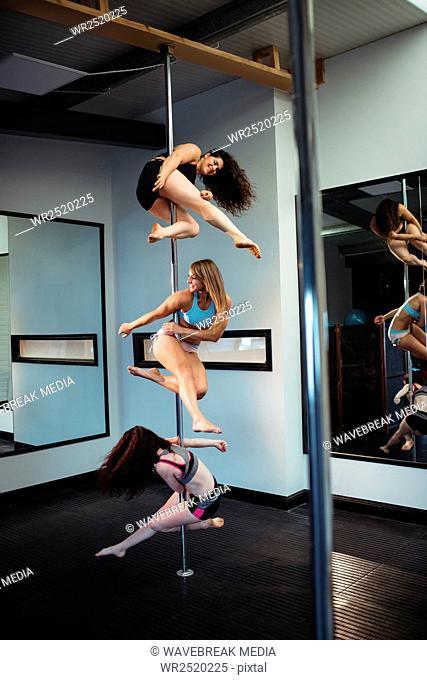 Pole dancers practicing pole dance