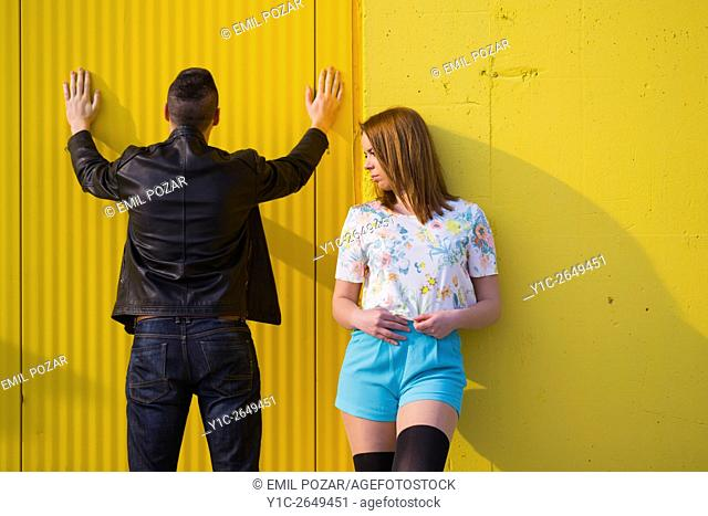 Teen girl and boy with hands up against wall