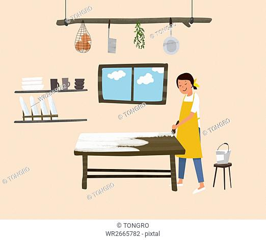 Smiling woman painting a table