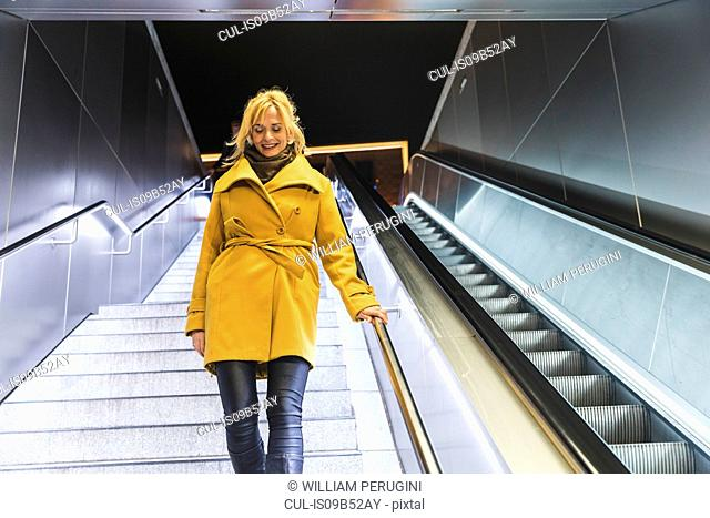 Woman moving down underpass stairway at night